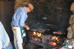 A man cooking over an open flame barbeque.